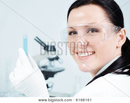 Closeup Of Smiling Female Researcher Holding Test Tube In Laboratory