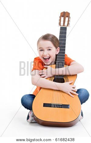 Cute girl sitting with acoustic guitar with bright emotions -  isolated on white background.