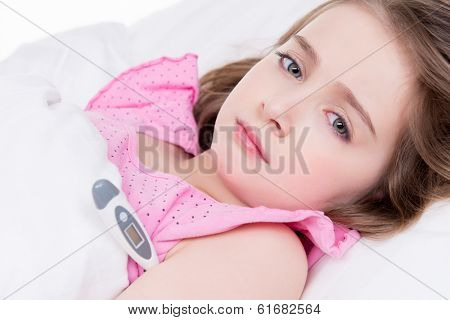 Little cute girl measures the temperature on a white background.