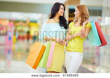 Portrait of happy girls in smart casual with paperbags having a chat in the mall