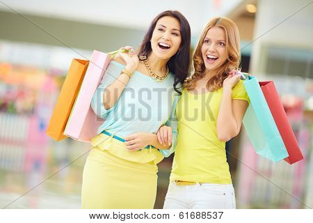 Portrait of surprised girls in smart casual with paperbags expressing astonishment