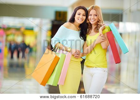 Portrait of happy girls in smart casual holding paperbags