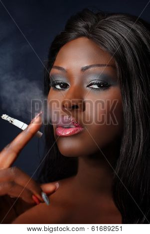Young woman of African smoking