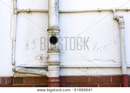Sewage And Water Pipes On Wall Of Residence