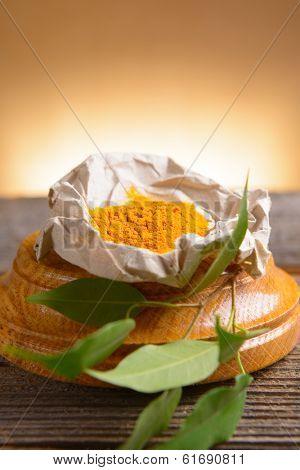 Tumeric powwder spice on wooden board with fresh leaves