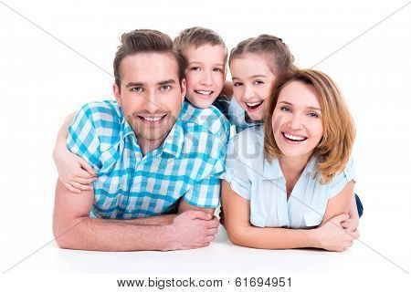 Caucasian happy smiling young family with two children lying down on the  floor