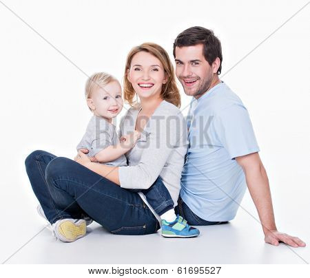 Photo of the happy young family with little child sitting on the floor - isolated on white background.