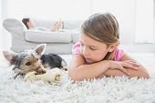 image of yorkshire terrier  - Little girl lying on rug with yorkshire terrier at home in the living room - JPG