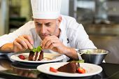 stock photo of pastry chef  - Closeup of a concentrated male pastry chef decorating dessert in the kitchen - JPG