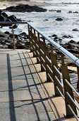 picture of balustrade  - Balustrade forming shadows and the rocky beach - JPG
