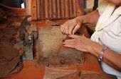 stock photo of cigar  - Woman makes and rolls cigars by hand in Trinidad Cuba