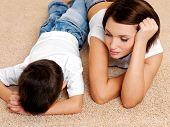 stock photo of nervous breakdown  - Photo of young mother and its disobedient guilty crying son lying on the floor - JPG