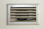 foto of hvac  - Small silver metal HVAC air vent with five slats in the white textured ceiling of an old home close up - JPG