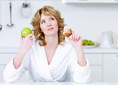 image of pie-in-face  - Thinking beautiful woman choosing between healthy food and caloric food  - JPG
