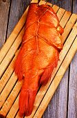foto of red snapper  - Delicious Smoked Red Snapper Fish on Cutting Board closeup on Rustic Wooden background - JPG