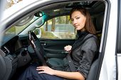 Portrait of beautiful young woman fastens a seat belt in the car - outdoors