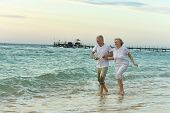 stock photo of amusement  - Amusing elderly couple went to the beach to have a walk by sea - JPG