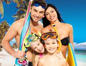 stock photo of suntanning  - Portrait of  happy fun beautiful family with two children at tropical beach with protective swimming mask - JPG