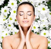 Portrait of beautiful young woman with healthy skin of face over flowers background . Beauty treatme