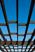 picture of pergola  - brown wooden pergola on a background of bright blue sky - JPG