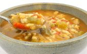 Spicy chicken soup in stoneware bowl with spoon poster