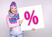 picture of outerwear  - Adult smiling  woman in warm outerwear  holds the white banner with per - JPG