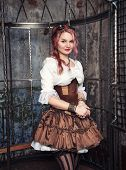 stock photo of gothic hair  - Beautiful steampunk woman with pink hair in the metal cage - JPG