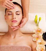 stock photo of angle  - Masseur doing massage the head of an adult woman in the spa salon - JPG