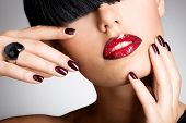 image of fingernail  - Closeup face of a woman with beautiful sexy red lips and dark nails  - JPG