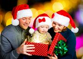 Happy family with one baby opens the  box with christmas gifts on the new year  holiday - indoors