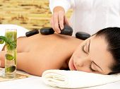 Woman having hot stone spa  massage of back in beauty salon