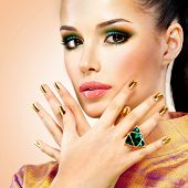 image of emerald  - Glamour woman with beautiful golden nails and emerald ring on hands - JPG