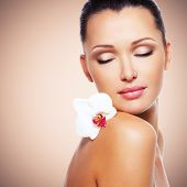Beauty face of  beautiful woman with a white orchid flower. Skin care treatment.