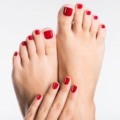 stock photo of pedicure  - Closeup photo of a female feet with beautiful red pedicure over white background - JPG
