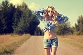 image of independent woman  - Portrait of Sexy Blonde Woman with Hands behind her Head Walking on Country Road - JPG