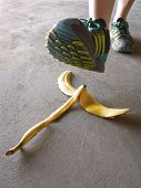 stock photo of slip hazard  - Person stepping on banana peel and slipping accident sidewalk floor - JPG