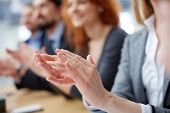 stock photo of glorify  - Cropped image of a businessperson applauding on the foreground - JPG