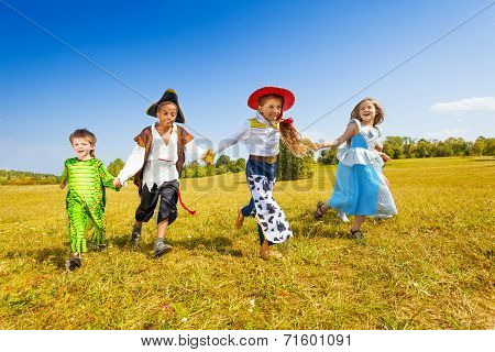Happy kids run wearing costumes in park