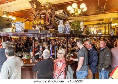 Glasgow, Scotland, UK - 23 August 2014: People drinking and watching football in The Horseshue Bar in Glasgow on the longest bar in Europe (104 feet and 3 inches).