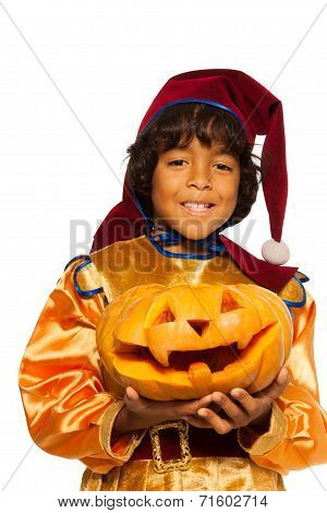 Boy in dwarf costume with carved pumpkin