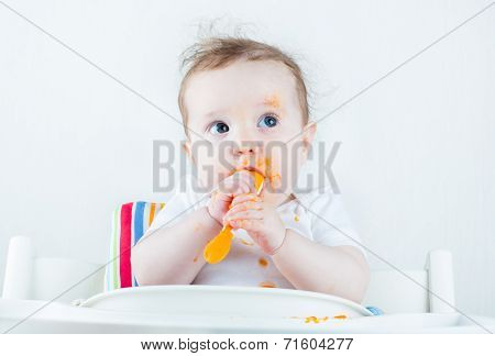 Sweet Messy Baby Eating A Carrot In A White High Chair