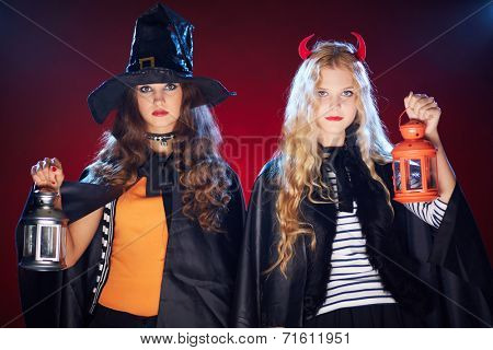 Halloween girls in black cloaks holding lanterns