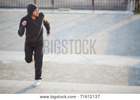 Portrait of young man in activewear jogging outside