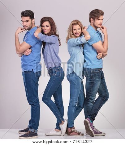 group of friends, men thinking and women leaning on them and smile, on grey background