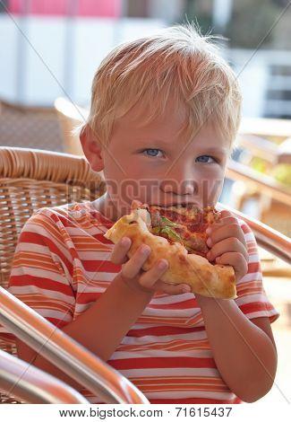 Little boy eating a pizza