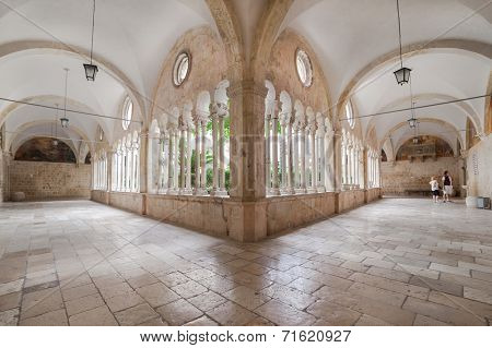 DUBROVNIK, CROATIA - MAY 26, 2014: Hallway around famous courtyard in the Monastery of the Friars minor. It is the most important work from the transitional period from the Romanesque to Gothic style