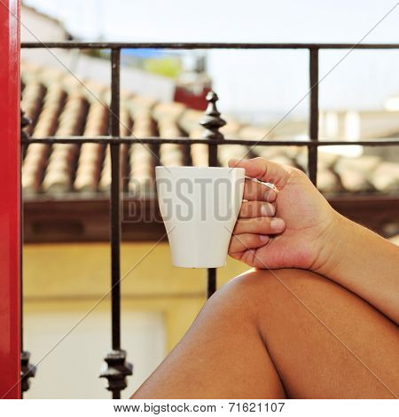 closeup of a young man in a balcony with a mug with coffee or tea in his hand