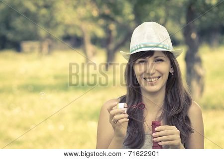 Young Woman Making Soap Bubbles In Summer Park.