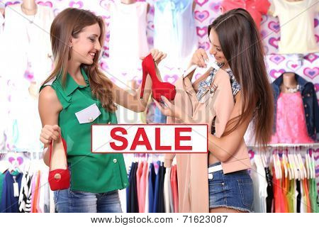 Concept of discount. Two beautiful young woman in shop