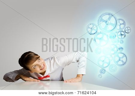 Businesswoman leaning on table and looking at cogwheels